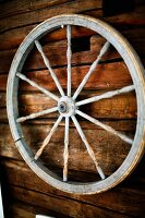 Old cart wheel with turned spoked hanging on wooden wall