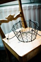 Wire basket with handle on old kitchen chair