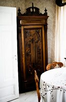 Antique cupboard with carved moulding behind dining set