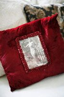Red velvet cushion with vintage, black and white picture in ruffled edging