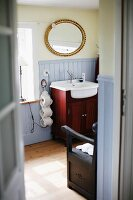 View through open door into bathroom; washstand with mahogany base unit below oval, gilt-framed mirror on wall painted pale yellow