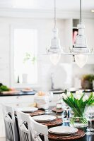 Retro, maritime pendant lamps and vase of tulips on festively set table in white, Scandinavian kitchen