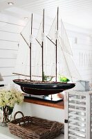 Splendid model of sailing boat on half-height wall in Scandinavian interior; wicker tray and vintage lantern in foreground
