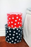 Red and black hat boxes with patterns of white stars on floor next to bed