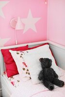 White, wooden child's bed with scatter cushions and teddy bear below wall lamp on pink wall with pattern of stars