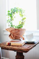 Ivy topiary ring, book and teacups on wicker side table