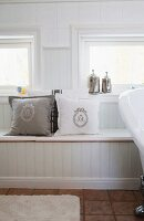 Monogrammed scatter cushions on window seat with storage space in white, country-house bathroom