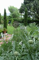 Bed of artichokes, metal garden ornament and cypress trees in background in garden