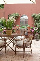 Delicate metal chairs and matching table on tiled floor of courtyard with potted plants against red-brown façade