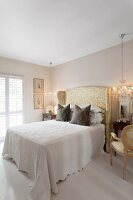 Elegant bedroom; white bedspread on double bed with tall headboard upholstered in glossy fabric next to chandelier