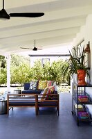 U-shaped bench with colourful cushions on veranda with white wooden ceiling and grey tiled floor