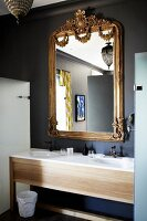 Modern washstand with twin sinks below mirror with ornate gilt frame on grey-painted wall