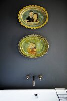 Ceramic plates on grey wall above vintage bath taps