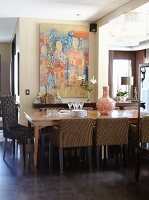Dining room with long table, upholstered chairs and large modern artwork on painted wall