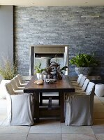 Antique wooden table, loose-covered chairs, tiled floor and stone-clad grey wall