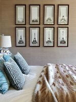 Double bed, beige textile wallpaper and gallery of pictures of Eiffel tower in elegant bedroom