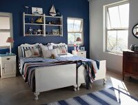 Twin beds pushed together against wall painted dark blue in bedroom with maritime ambiance