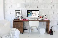 Workspace with white shell chair, desk, filing cabinet on castors and monitor against white mural wallpaper with bookcase motif