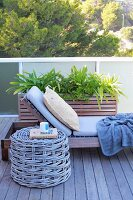 Chunky wicker stool next to modern, wooden sun lounger with cushions on balcony with a view