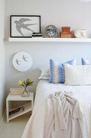 Scatter cushions arranged on bed, modern white bedside table, wall lamp with swallow motif and ornaments on floating shelf