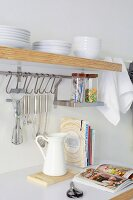 Detail of kitchen counter; utensils hanging on wall below white crockery on wooden shelf