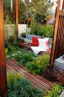 Terrace with wooden decking between beds of ornamental grasses and bench with cushions