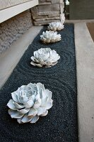 Rosettes of succulents in bed of gravel raked into circular pattern