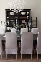 Chairs with pale grey loose covers around dining table below chandelier; antique shelves in background