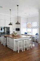 Free-standing island counter with white bar stools in open-plan country-house kitchen with dining set in window bay