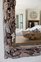 Detail of mirror with driftwood frame and reflection of interior