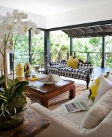 Sofas around mahogany coffee table; open terrace doors in background with view into garden