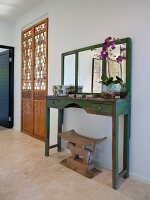 Vintage wooden washstand with mirror stained green next to carved wooden double doors
