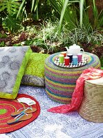 Pouffe, raffia stool and floral floor cushions on picnic blanket in garden