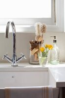 Sink with mixer tap and washing-up brushes in glass container