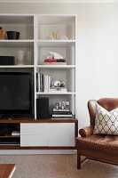 Brown leather armchair next to modern, white shelving