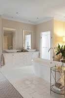 Elegant bathroom with free-standing bathtub on tiled floor and washstand with twin countertop basins