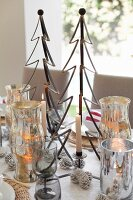 Lit candles, Christmas decorations, stylised metal Christmas trees and silver tealight holders