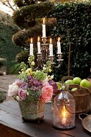 Candle lantern and flower arrangement in front of candelabra on rustic garden table
