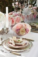 Elegant place settings and arrangements of pink and white roses on festive table