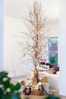 Gifts below delicate Christmas tree made from palm fronts decorated with white paper flowers