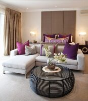 Round, transparent coffee table in front of sofa combination in elegant, beige bedroom with purple accents