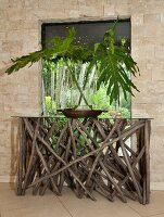 Glass vase of leaves on console table made from rustic sticks and glass top below window