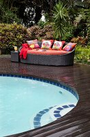 Brown outdoor sofa with colourful cushions on curved wooden pool deck in summer garden