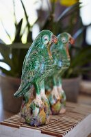Painted, ceramic parrot figurines in front of mirror