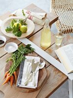 Cutlery and vegetables on wooden board next to lemonade and lemons on wooden table