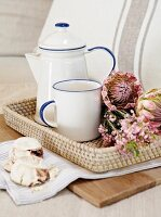 Rustic mug and coffee pot next to protea flowers on wicker tray