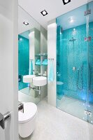 Sink mounted on mirrored wall next to glazed, floor-level shower area with pale blue mosaic tiles on wall