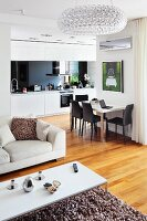 White coffee table on flokati-style rug and pale sofa in front of dining table against wall in open-plan fitted kitchen