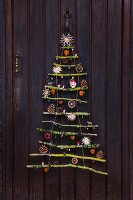 Stylised Christmas tree made from mossy branches with natural decorations and straw stars hanging on front door