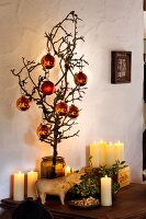 Gnarled fruit tree branch with Christmas tree baubles in glass vase; lit candles and wooden cow